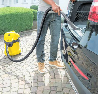 Cleaning car using yellow Karcher vacuum cleaner